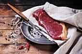 Rohes Steak auf Metallteller an altem Holztisch
