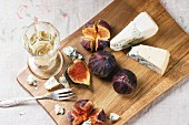 Figs with blue cheese, white wine and crackers on wooden cutting board