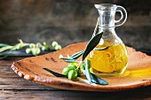 Bottle of olive oil with olive branch in handmade clay plate over wooden table