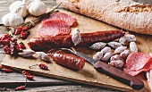 Set of salami sausages served with fresh bread, garlic and red hot chili peppers on wooden cutting board