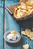 Basket with potato chips with plate of sause and sea salt over blue wooden table