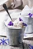 Ice cream, served in little metal pail with sugared violets on old wooden table