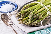 Bunch of young green asparagus on vintage tray, ceramic plate of sea salt and silver cutlery