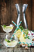 Fresh homemade lemonade with lemon, lime and mint in glasses with vintage cocktail tube over wooden table