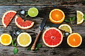 Set of sliced citrus fruits lemon, lime, orange, grapefruit with mint, ice and vintage knife over wooden background