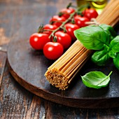 Spaghetti and tomatoes with herbs on an old and vintage wooden table