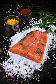 Piece of salted salmon, served with dill and spices on sea salt over black wooden table