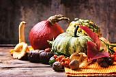 Kürbisse, Nüsse, Beeren und Pilze auf alten Holztisch