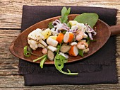 Lukewarm seafood salad with vegetables and giant capers