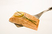 Salmon filet with roasted lemon slice and chives on a spatula