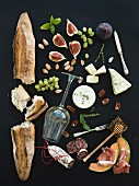Baguette, glass of white, figs, grapes, nuts, cheese variety, meat appetizers and herbs on black grunge background