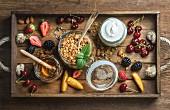 Healthy breakfast ingredients. Oat granola in open glass jar, fruit, yogurt, honey, berries and mint in wooden tray