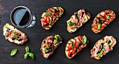 Brushetta snacks for wine. Variety of small sandwiches and glass of red wine on dark rustic wooden backdrop