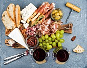 Prosciutto di Parma, salami, bread sticks, baguette slices, olives, sun-dried tomatoes, grapes
