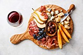 Prosciutto ham, Parmesan, Blue cheese, Cantaloupe melon and Olives on olive wood serving board