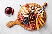 Antipasti-Platte mit Schinken, Käse, Obst und Oliven dazu ein Glas Rotwein