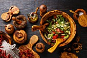 Fresh vegetable salad in olive wood bowl and wooden tableware on black burned wooden background