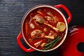 Stewed lamb on bone stewed in tomato sauce in cast iron pot on burned black wooden background