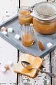 Toast with homemade caramel sauce for breakfast, served with spoon, jars and sugar cubes