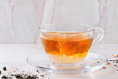Milk dissolves in glass cup of hot tea on saucer with dry green and black tea leaves