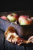 Getrocknete Apfelringe auf Schnur an alter Backform, Hintergrund Äpfel