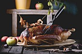 Roast stuffed goose with meat fork in on ceramic plate with ripe apples over wooden kitchen table