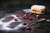 Eclairs and trace of the eclair in sugar powder, with dry tea rose buds and vintage cutlery over dark background