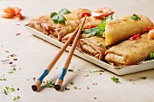 Fried spring rolls with vegetables and shrimps, served with spicy sauce and chopsticks over white wooden background