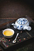 Traditional japanese teapot and cup of green tea, served on bamboo tray with dry tea variations over dark background