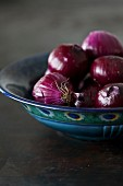 Peeled red onions in a bowl