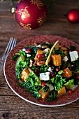 Festive kale, roasted sweet potatoes and parsnips salad with Feta cheese, pecans and pomegranate in a bowl