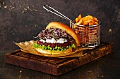 Beet burger with soft cheese, radish sprouts and potato wedges on dark background
