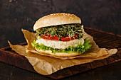 Cauliflower burger with clover sprouts on dark background