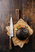 Black Salmon burger with cream cheese and arugula on cutting board on dark wooden background