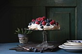 Vintage cake stand with Meringue dessert Pavlova with fresh blackberries and raspberries