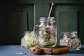 Fresh Garlic and Radish Sprouts in glass mason jars with fork inside, standing on small chopping board
