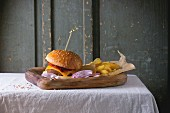 Wooden plate with fresh homemade burger and grilled potatoes over white tablecloth with gray wooden background