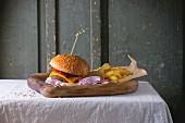 Selbstgemachter Burger mit Pommes auf Holzbrett und rustikalem Tisch
