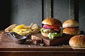 Selbstgemachte Burger mit Pommes und Ketchup auf Holzuntergrund