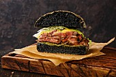 Cut in half Roast beef Burger with sliced Pastrami on dark background
