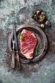 Rohes Striploin Steak mit Rosmarin und Vintage-Besteck auf Teller