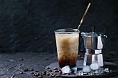 Glass of ice coffee with cream and milk, served with coffee beans, ice cubes and coffee pot on slate stone board