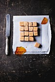Fudge candy and caramel on baking paper, served with vintage knife over dark background