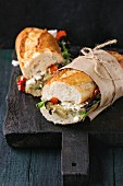 Two half of vegetarian baguette submarine sandwich with grilled eggplant, pepper and feta cheese
