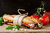 Papered vegetarian baguette submarine sandwich with grilled eggplant, pepper and feta cheese on wooden chopping board