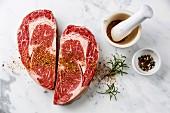 Zwei rohe Ribeye Steaks in Herzform mit Kräutern und Gewürzen