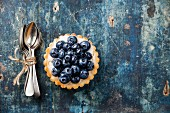 Blueberry tart and Bunch of teaspoons on blue wooden background