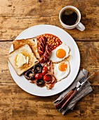 Full English Breakfast with fried eggs, sausages, bacon, beans, toasts, tomatoes and mushrooms
