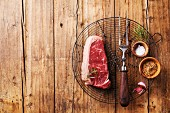 Raw fresh meat of South American premium beef New York steak on Wire Cooling Rack on wooden background