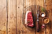 Ein rohes New York Strip Steak mit Fleischgabel und Gewürzen (Aufsicht)